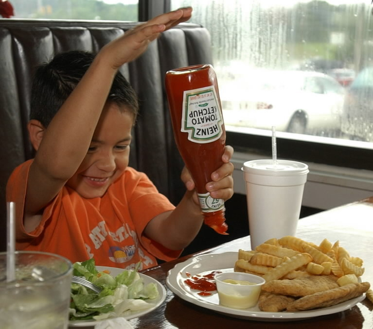 Child getting all the ketchup out of the Heinz bottle